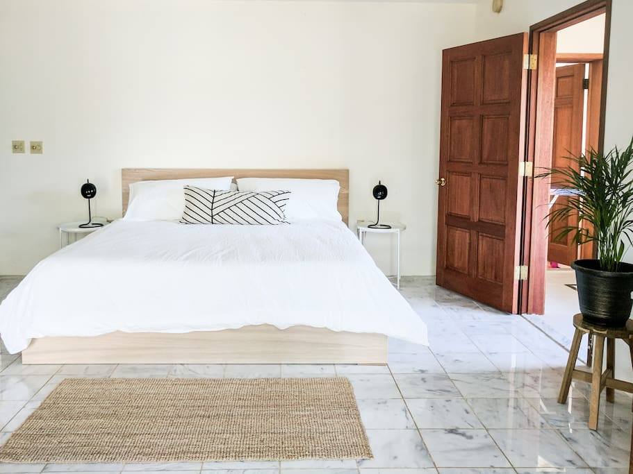 Large spacious bedroom with King size bed and high ceilings.