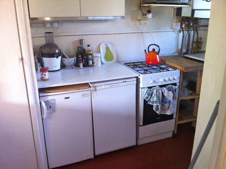 Kitchen with cooker, kettle, microwave, fridge, freezer and washing machine.