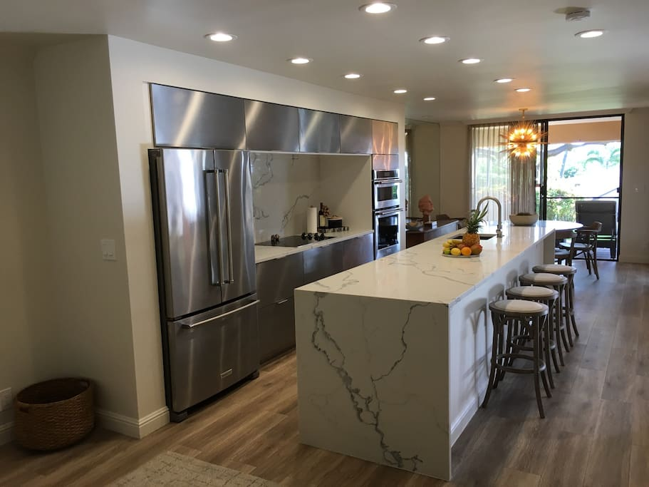 Newly remodeled kitchen with stainless steel appliances and marble counters.