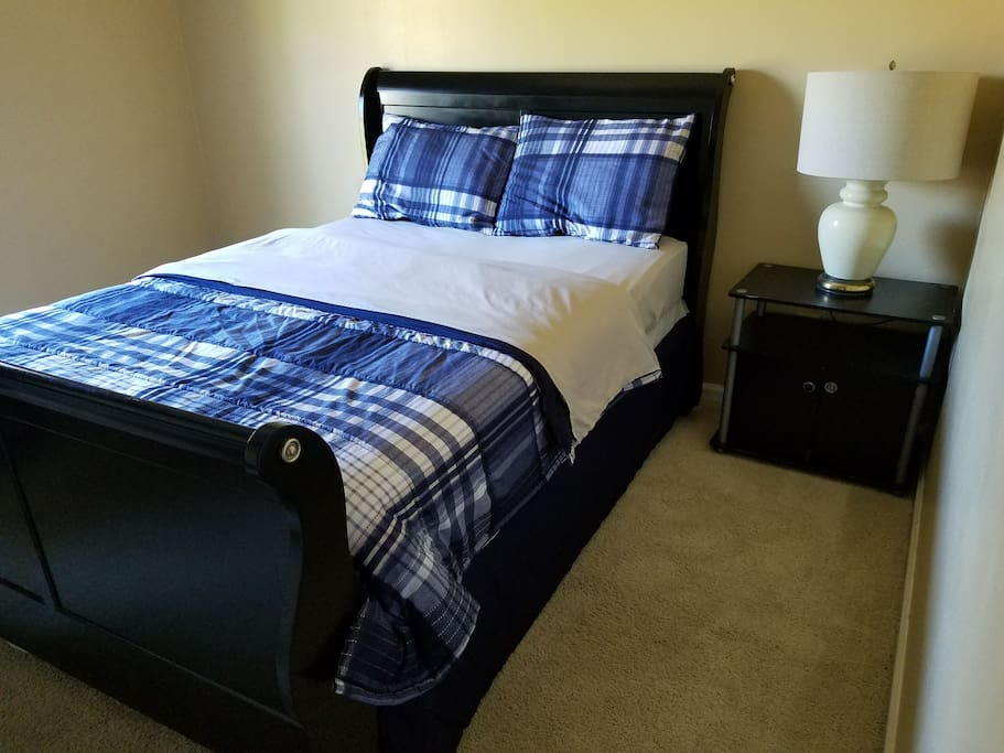 Queen size bed, nightstand, and a lamp