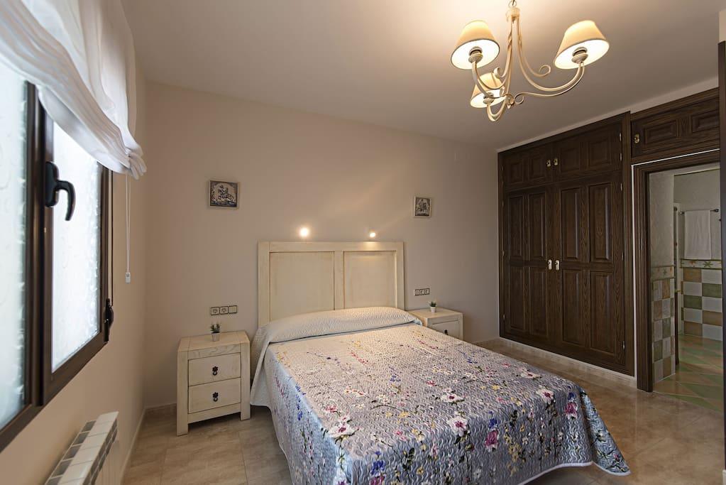 DOMINUS Dormitorio equipado con una cama de matrimonio de 150 cm, sofá de tres plazas, armario empotrado y baño en suite