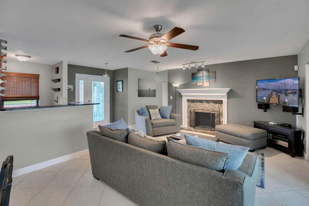 Gather the group in the living room, which seats 6 on modern upholstered furniture.