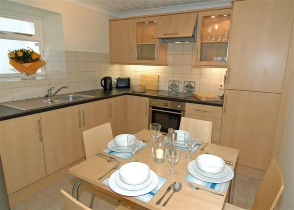 Kitchen with table for 4, fridge freezer, dishwasher and washing machine