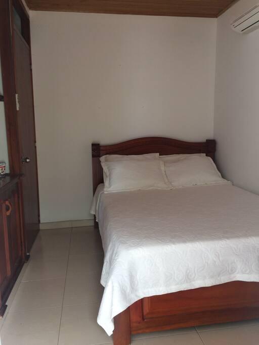 Habitacion con una cama doble ,aire acondicionado,tv y baño compartido
