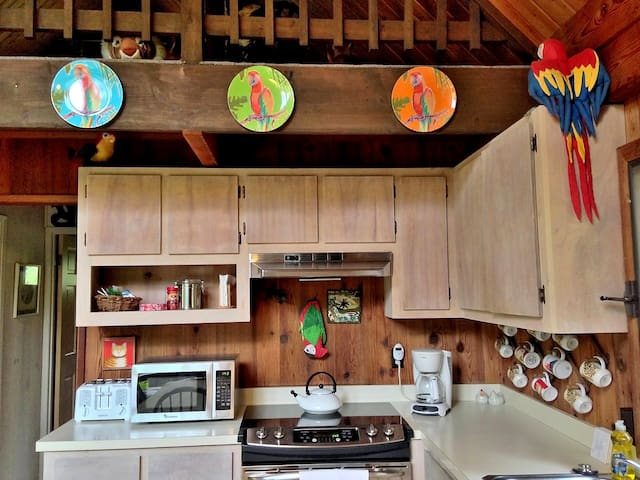 The kitchen is small but fully equipped. There is a full-size refrigerator (at left, it just fits in the cubby hole beneath the stairs), full-size oven and electric stove top, toaster, microwave, coffee maker, and double sink with garbage disposal. There is even a rice maker in the cupboard.