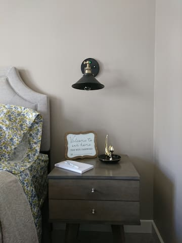 Bedroom nightstand has a pull out drawer. With a WiFi password reminder in a frame. Also sits on the nightstand is a cat jewelry dish to hold your rings. Plus a pen and note pad to jot down any notes.
