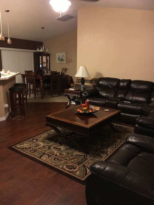 Shared living room space with large leather sectional, coffee table, and television with Netflix