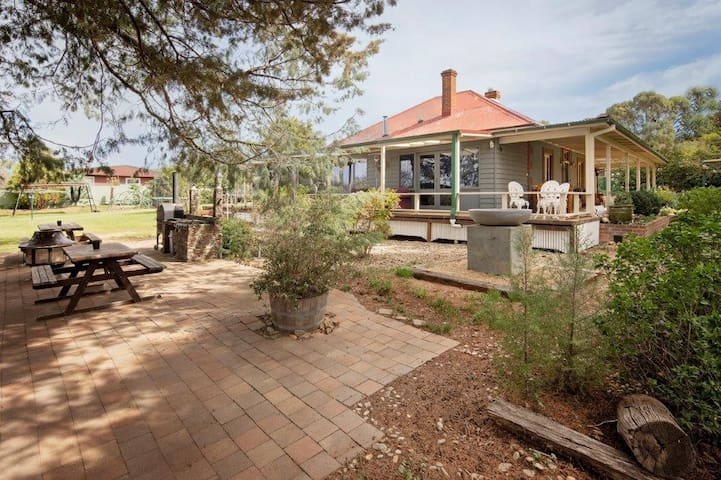 BBQ area with Pizza Oven, Firepit and two large picnic benches directly across from the verandah.