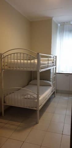 Habitación doble con litera y baño compartido