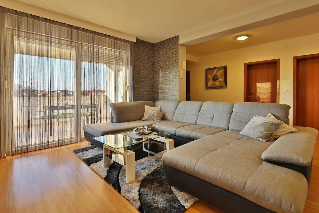 Living room with access to a furnished balcony.