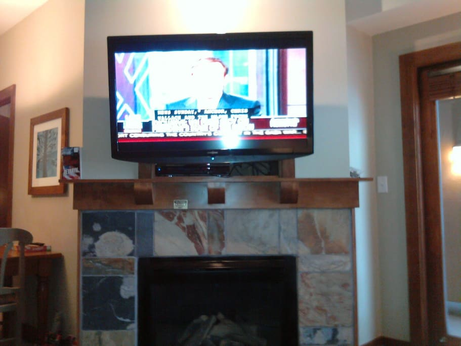 """New 47"""" HDTV w/ Blue-Ray/DVD player, with the gas fireplace below and glass door to the balcony to the right.  15 or so DVD's on shelf for your viewing."""
