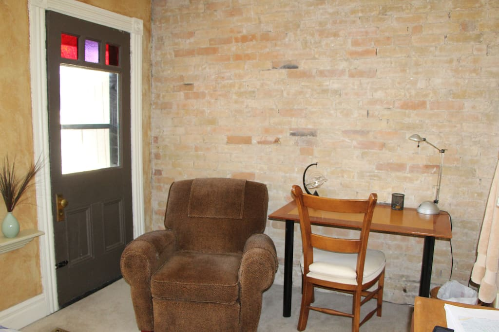 Against the exposed brick, the desk provides you a nice workspace. (Door is to Juliet Balcony).