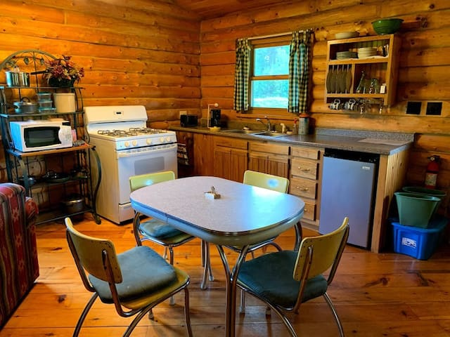 Kitchen with mini fridge, full-sized stove/oven, microwave, coffee maker, toaster and dining table.