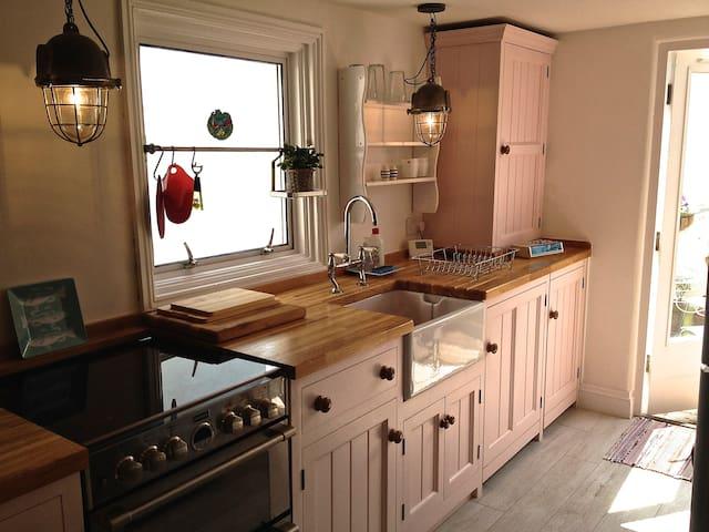 Bright bespoke kitchen with cooker, microwave, fridge/freezer, washing machine & dishwasher. Leads to sunny balcony.