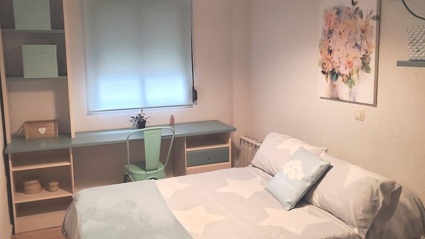 Habitación con cama de matrimonio y zona de trabajo.
