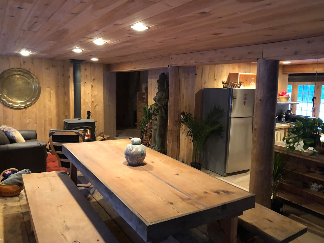 Handmade table and handmade benches that can hold 8-10 people, awesome stove with the cozyness of a fireplace, rustic barn flooring... all very spacious
