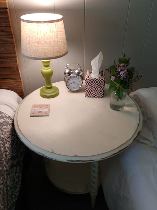 side tables, lamp, tissue, fresh flowers, alarm clock and coaster.