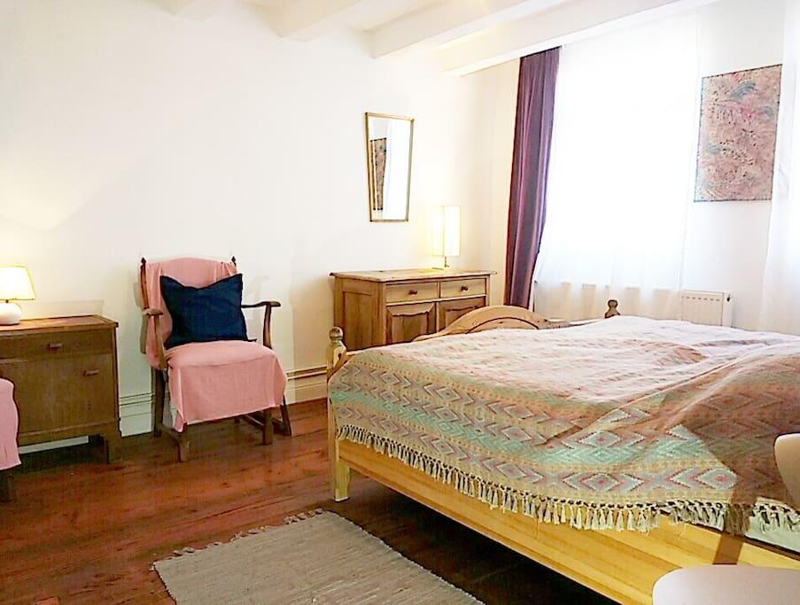 individuell eingerichtetes Zimmer mit Doppelbett