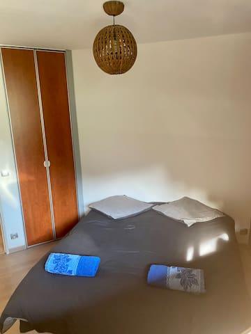 La chambre équipée d'un lit double en 140, et son placard de rangement.  The bedroom is equipped with a double bed (140cm) and a storage cupboard.