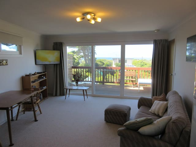 Spacious, comfortable living room with TV, couch and dining table. Sliding door opening onto the large balcony with ocean view