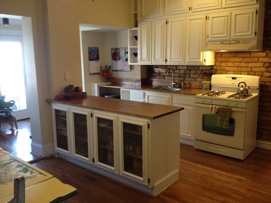 Large light filled kitchen with butcher block counter tops and lots of storage