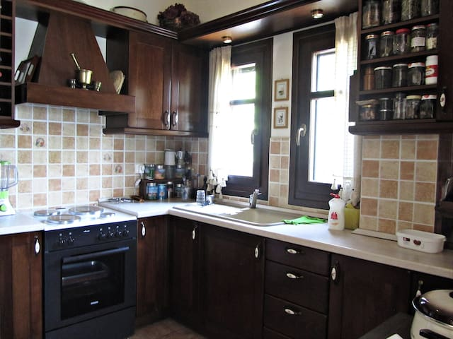 The kitchen with a coffee maker, a fridge, an oven and all the necessary equipment for cooking