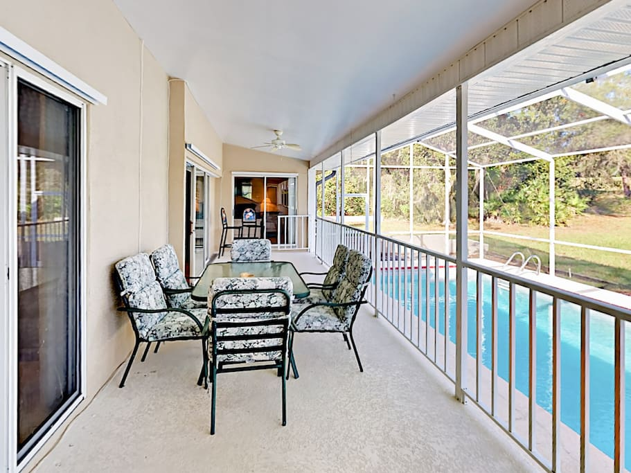 Dining area with seating for 6, overlooking screened pool.