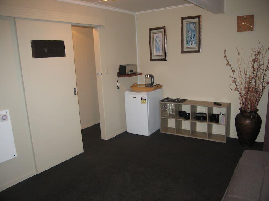 Lounge/kitchenette with sofa bed, TV, fridge, kettle, toaster, cutlery & crockery.