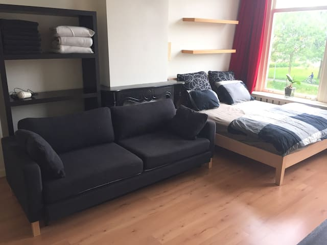 Double bed and couch with view of the canal.