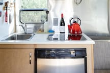 The 16' Airstream kitchenette includes a sink, 2 propane burners, a fridge, and a microwave. There is also a propane BBQ outside.