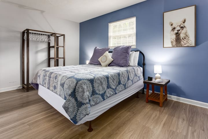The bedroom has a queen size bed, nightstands with reading lamps and a wardrobe for hanging your clothes.
