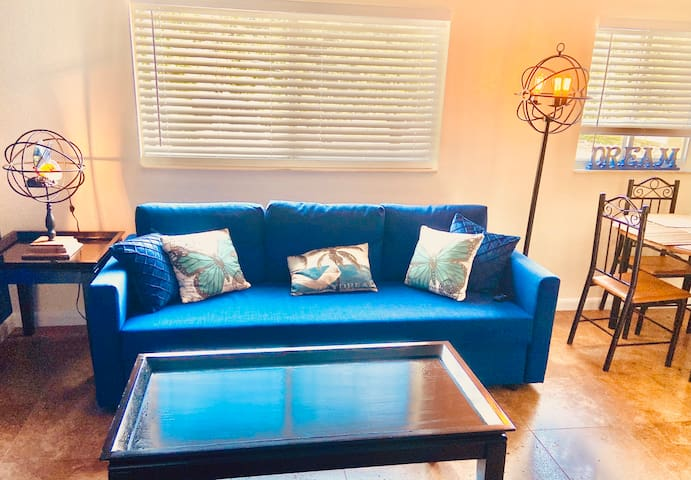 Stylish, comfortable, interior-designer created living room with plush sofabed and plenty of decor lighting. Open the blinds to see palm trees sway in the Florida breeze and brilliant sunshine.