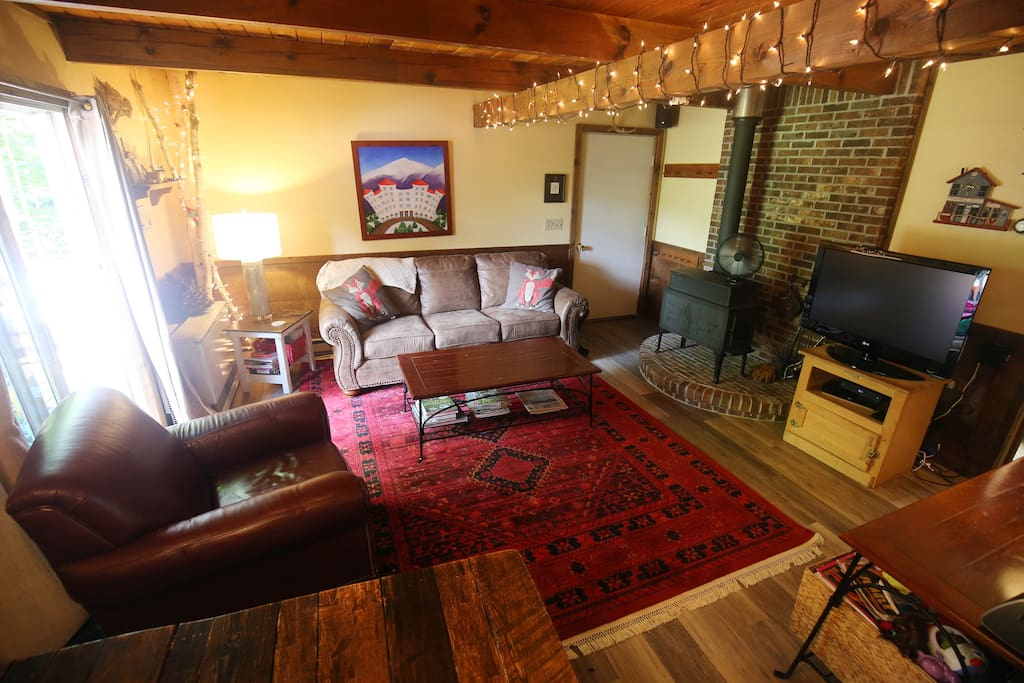 Living/dining area features wood burning stove, couch, chair, and dining for 6.