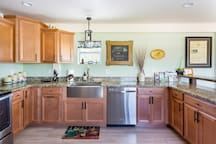 Warm, wood cabinetry, stainless appliances, and a large farm sink can handle any culinary adventures!