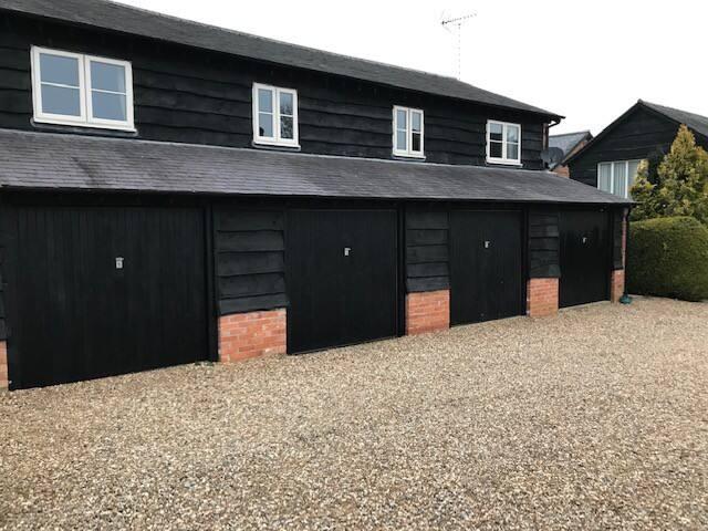 4 black garage doors in car park