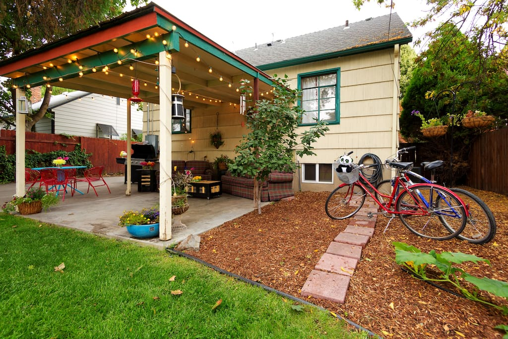 Open patio with comfortable outdoor furniture, coffee tables, patio lights, and BBQ grill.