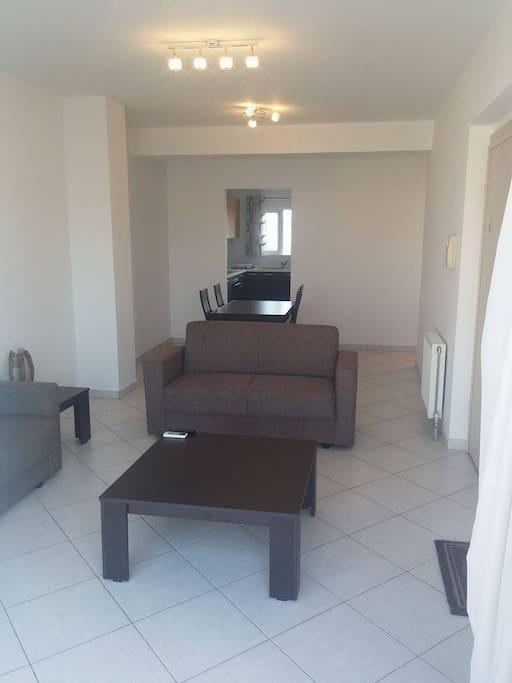 Living Room, Equipped with two new couches, new flat screen TV, new dinning table and Air Condition Unit.