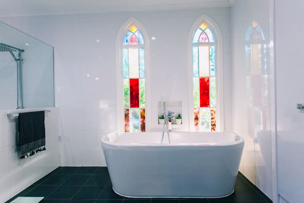 Immerse yourself in a deluxe double bath whilst the light filters through the original church windows. Large family size bathroom with open shower and  bath.