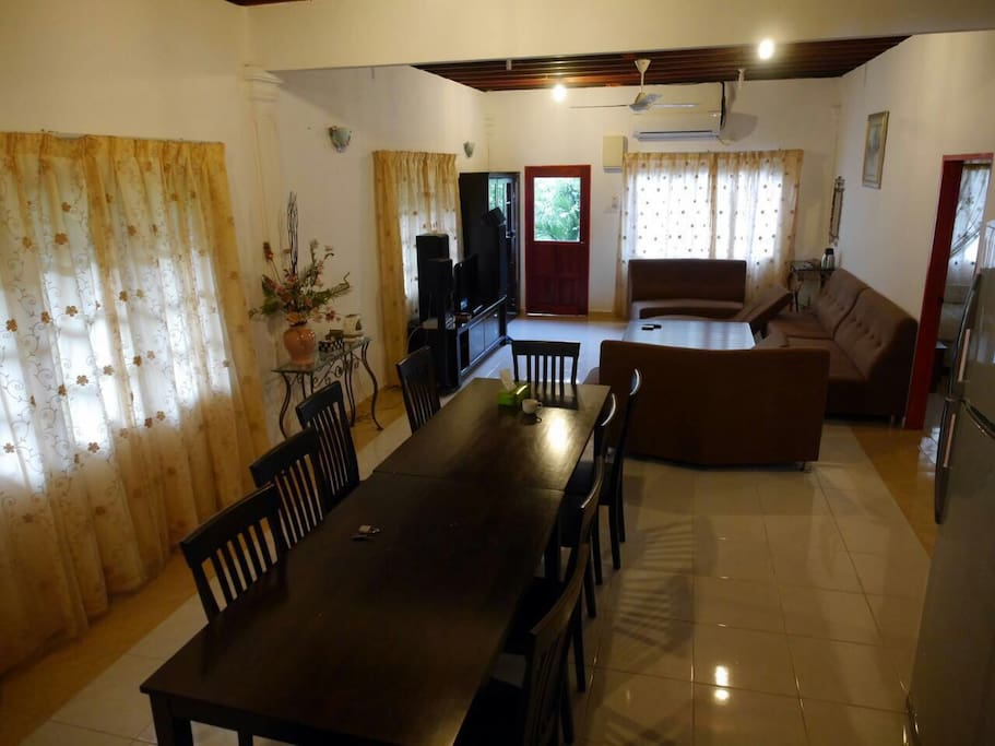 Relaxing indoor setup includes TV with Astro, 8 seat dining table and comfortable, well maintained couches.