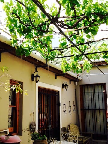 Facade of a vintage cottage built in 1890 complete with wooden floors and ceilings - vine overhead cools the alfresco cafè- style courtyard for sunning and chilling