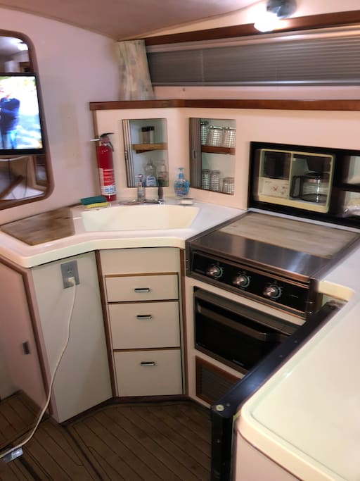 Galley with three burner electric range. Microwave, coffee maker, refrigerator, complete set of dishes, pots, pans, stainless ware, glasses, cups and much more.