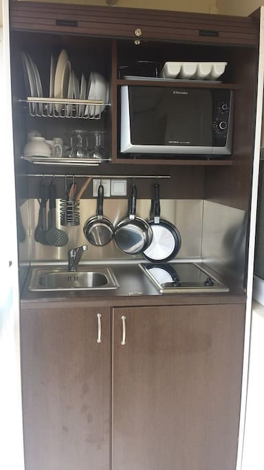 cuisine équipée : couverts, assiettes, poêle, réfrigérateur