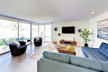 """A comfy sectional and 2 armchairs surround the 55"""" Roku TV in the living area. Complimentary Wi-Fi provided."""