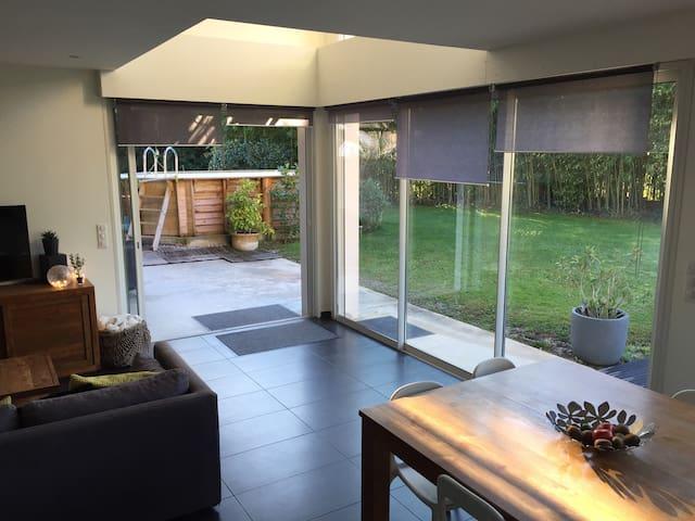 Vue du salon sur la terrasse couverte et la piscine