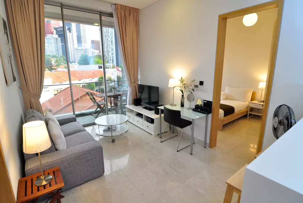 Living room with sofa bed, open kitchen, fast wifi, cable TV, large balcony and view of heritage shophouses.