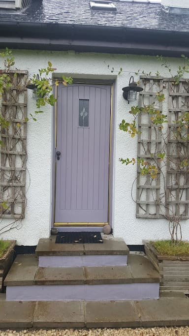 The lilac front door leading to the private double apartment.