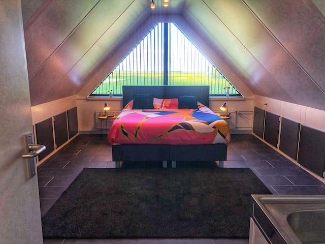 grote slaapkamer met uitzicht op achterliggend natuurgebied