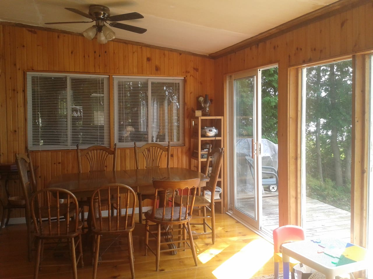 This is the dining area of the cottage, that is open-concept, with a full wall of large sliding doors that open up to the lakefront.