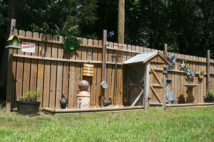 Whimsically decorated yard, with privacy fence on a rural country road.  Find your supplied firewood inside the small structure shown.  There are no neighbors on the other side of the fence...it blocks the barely traveled, rural, blacktop road.