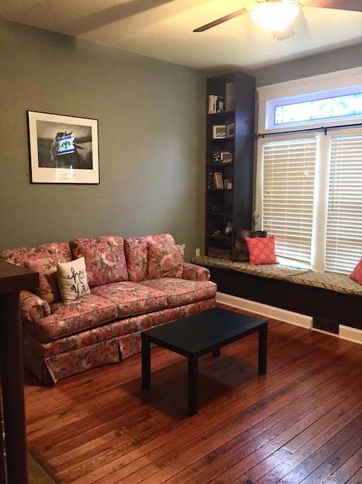 Front room with sofa and built in bookcases with reading nook